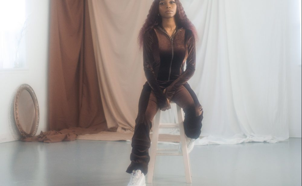 Osé sitting on chair in studio