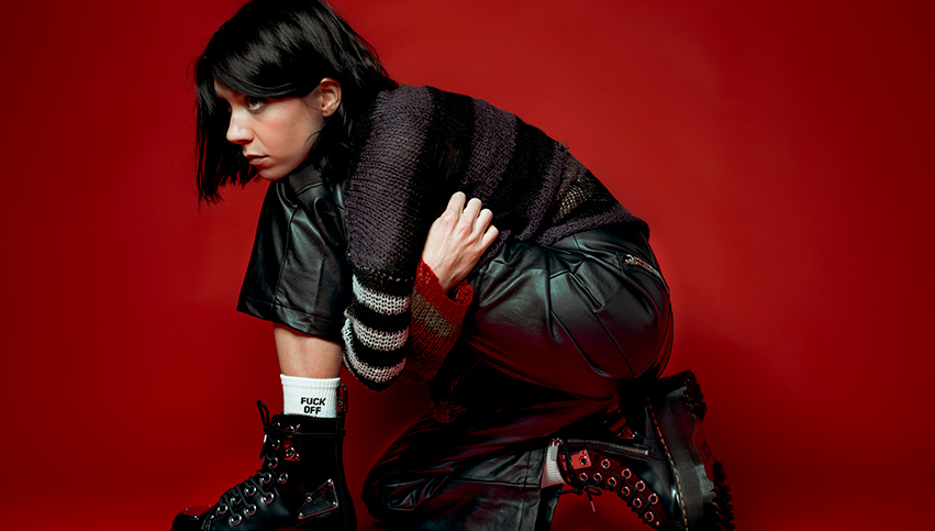 K.Flay crouched down in leather in a red room
