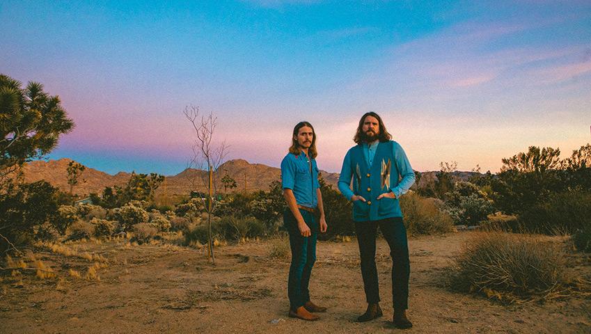 Bros bandmates posing in desert at sunset or sunrise