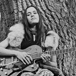 Bebe Buckskin posing with guitar in front of tree