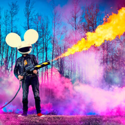 deadmau5 standing in blue and pink lit outdoor setting with a blowtorch.